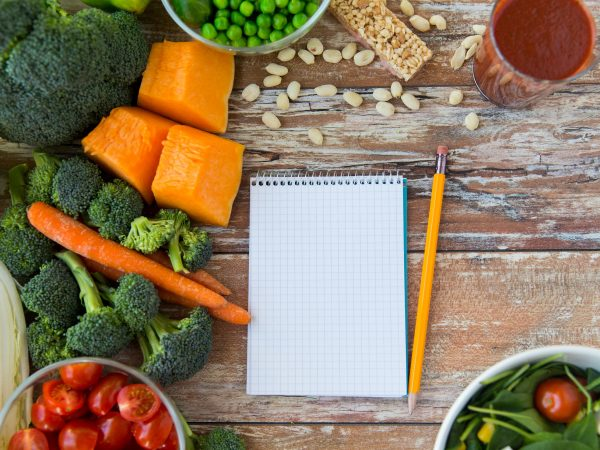 healthy eating, vegetarian food, advertisement and culinary concept – close up of ripe vegetables and notebook with pencil on wooden table
