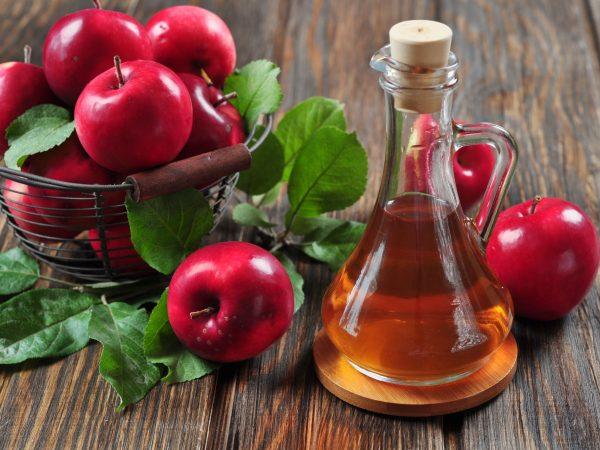 21757250 – apple cider vinegar in glass bottle and basket with fresh apples