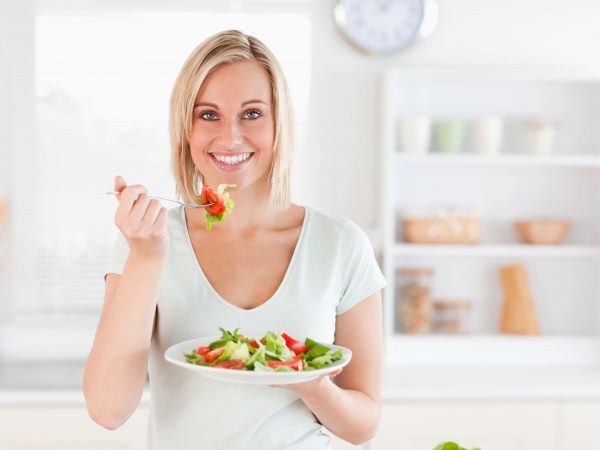11200063 – close up of a gorgeous woman eating salad in the kitchen