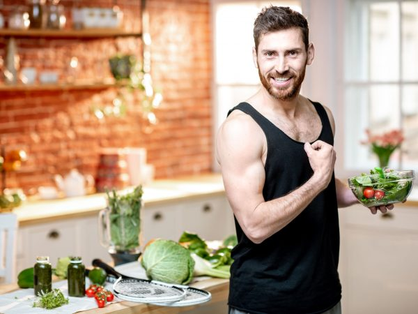 Portrait of a handsome sports man showing muscles, eating healthy vegetarian salad on the kitchen at home